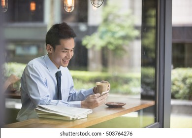 Asian Businessman with a cup of coffee reading his smart phone in a cafe.