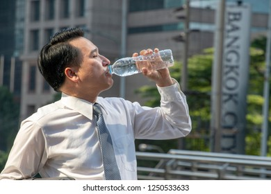 Asian businessman is drinking still water from bottle with building background