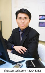An Asian businessman facing the camera in his office.