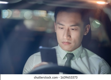 asian businessman feel tired and depressed after using smartphone in the car