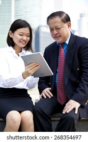 Asian businessman & female executive using tablet