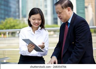 Asian businessman & female executive using tablet