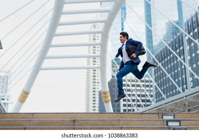 Asian businessman in formal wear holding briefcase while running and jump in the city on a background of building. late for work concept