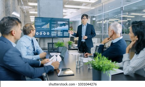 Asian Businessman Gives Report/ Presentation to His Business Colleagues, Pointing at the Results Showing Statistics, Pie Charts and Company's Growth On Wall TV Screen.