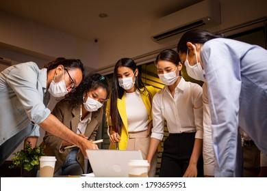 Asiatische Business-Mann-Gruppe diskutieren über ihr Projekt in der Nacht im Büro.Corporate mit neuen Normalität. Die thailändischen Leute tragen eine Maske, um ansteckende Krankheiten in der Gesellschaft zu verhindern.