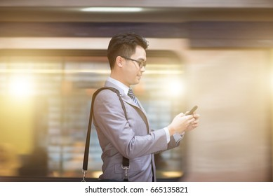 Asian businessman hand using smart phone in subway station, train passing by at the background.
