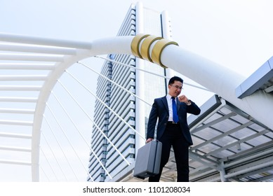 The asian businessman has holding a black bag and looking on watch in hurrying time.