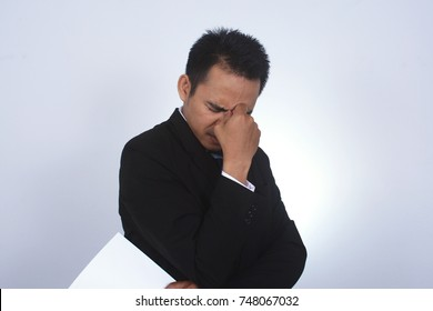 Asian businessman with headache pinching back of his nose and holding blank paper with left hand