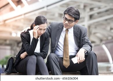 Asian businessman help woman in stress situation while sitting, business stressful concept.