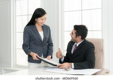 Asian businessman and his assistant Secretary in his office. The Secretary brought the boss documents to sign,Boss signs at documents and thumb up.