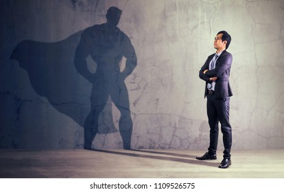 Asian businessman with his shadow of superhero on the wall. Concept of powerful man