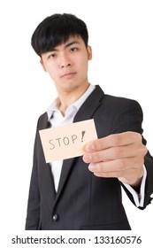 """Asian businessman holding a card written on """"stop"""", closeup portrait."""