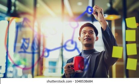 asian businessman holding coffee mug and writing data on transparent board
