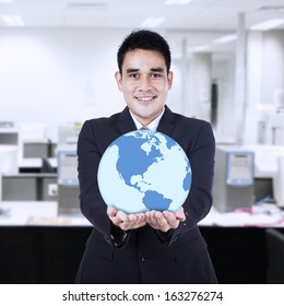 Asian businessman holding a globe at office