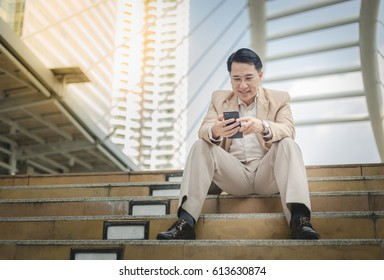 Asian businessman holding using his phone and sitting on the staircase