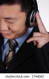 An asian businessman listening music.
