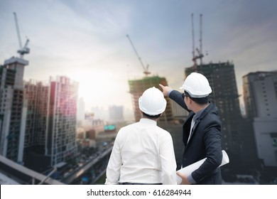 Asian businessman looking and point to finger away and engineer architect hold construction industrial plan background for working together as team concept, back view