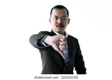 Asian businessman or manager or boss thumbs down showing to camera isolated in white background (Selective focus on hand). Unsuccessful business concept.