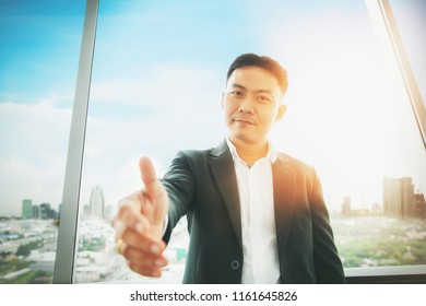 asian businessman with open hand ready for deal or welcome to the team