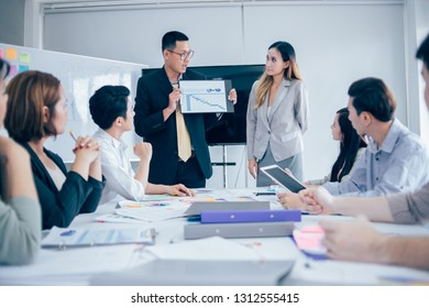 Asian Businessman presenting to colleagues at a meeting.Successful team leader and business owner leading informal in-house business meeting. Businessman working on laptop in foreground.