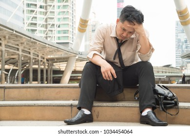 Asian businessman professional failed or upset in his job and sitting on staircase.