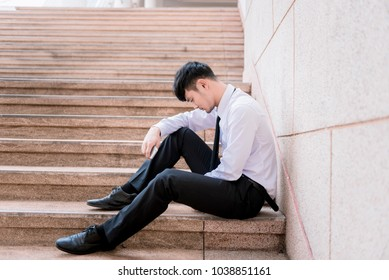 Asian businessman professional failed or upset in his job and sitting on staircase. Business problem concept.