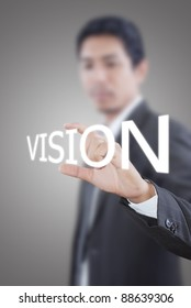 Asian businessman pushing vision word on a touch screen interface.