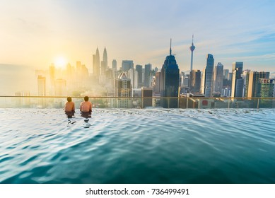 Asian businessman relax in swimming pool on roof top behind beautiful city view kuala lumpur in sunrise sky, Malaysia