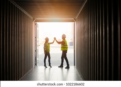 Asian businessman and Asian secretary celebrate after working success  iin yard in container Cargo freight ship in shipyard for Logistic Import/Export background