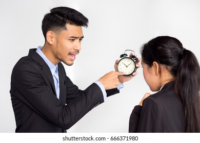 Asian businessman showing alarm clock and complaining at employee about working late on white background, punctuality concept