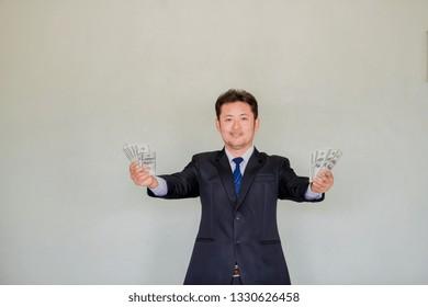 Asian businessman showing hundred dollar