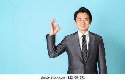 Asian businessman showing OK hand sign.