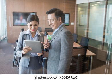 Asian businessman showing something on the digital table to his colleague