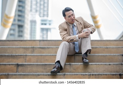 Asian businessman sit down on the step and hold his knee because of his knee pain