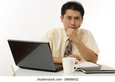 Asian businessman sitting at computer thinking