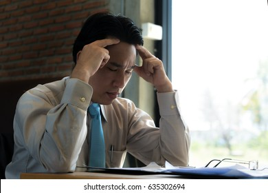 Asian businessman sitting and thinking in cafe, looking frustrated and depressed.