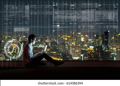 Asian businessman sitting and using the laptop showing digital virtual screen over the cityscape background at night time, Business technology and innovation concept