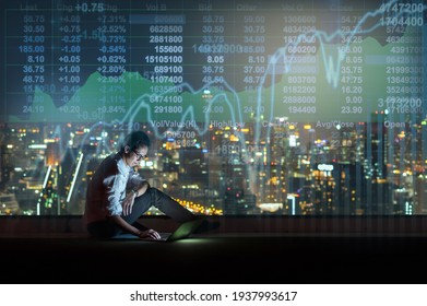 Asian businessman sitting and using the smart mobile phone showing the Stock market chart over the cityscape background at night time, Business  technology and trading concept