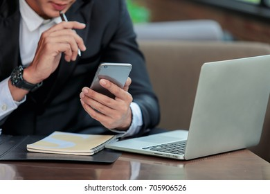 An Asian businessman sitting and working on a phone