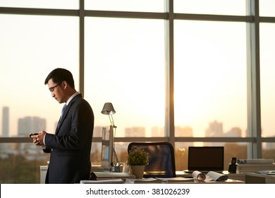 Asian businessman with smartphone is going to work in office after sunset