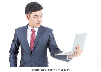 Asian Businessman standing and holding laptop on White Background with Success feeling, Business Success Concept, isolated on white background.