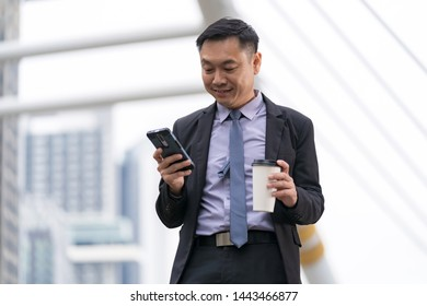 Asian Businessman standing and holding mobile phone with business office buildings in the city background