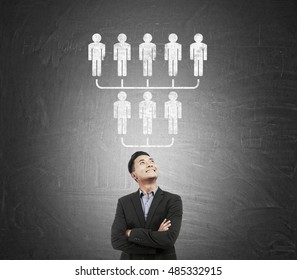 Asian businessman standing near blackboard with upside down pyramid. Concept of MLM