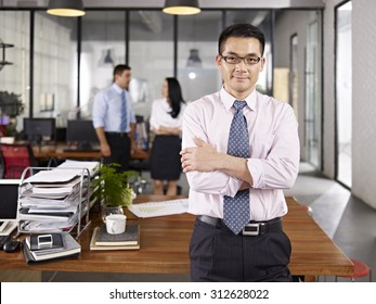 asian businessman standing in office arms crossed with multinational colleagues talking in background.