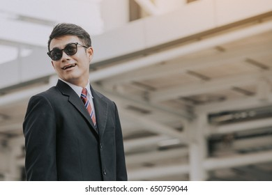 Asian Businessman standing on Modern city background., new age businessman concept