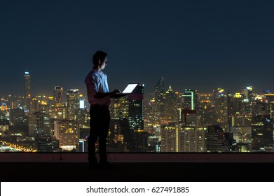 Asian businessman standing and using the laptop over the cityscape background at night time, Business success and technology concept
