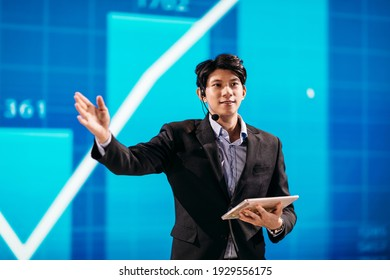 Asian Businessman Stands on Stage for Business Presentation
