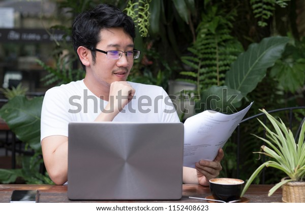 Asian businessman or student wearing casual white shirt working with document paper in green garden cafe using laptop. Coffee shop, nature, business, revision, education and study concept.