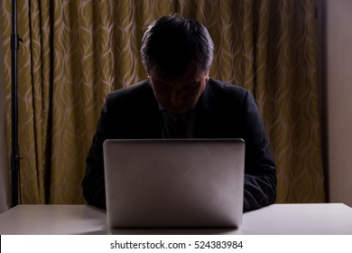 Asian businessman in suit attempting to hack computer network in dark
