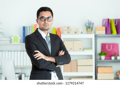 Asian businessman in suit looks good standing cross his arm in front of office desk. Concept for small business startup Initiative.